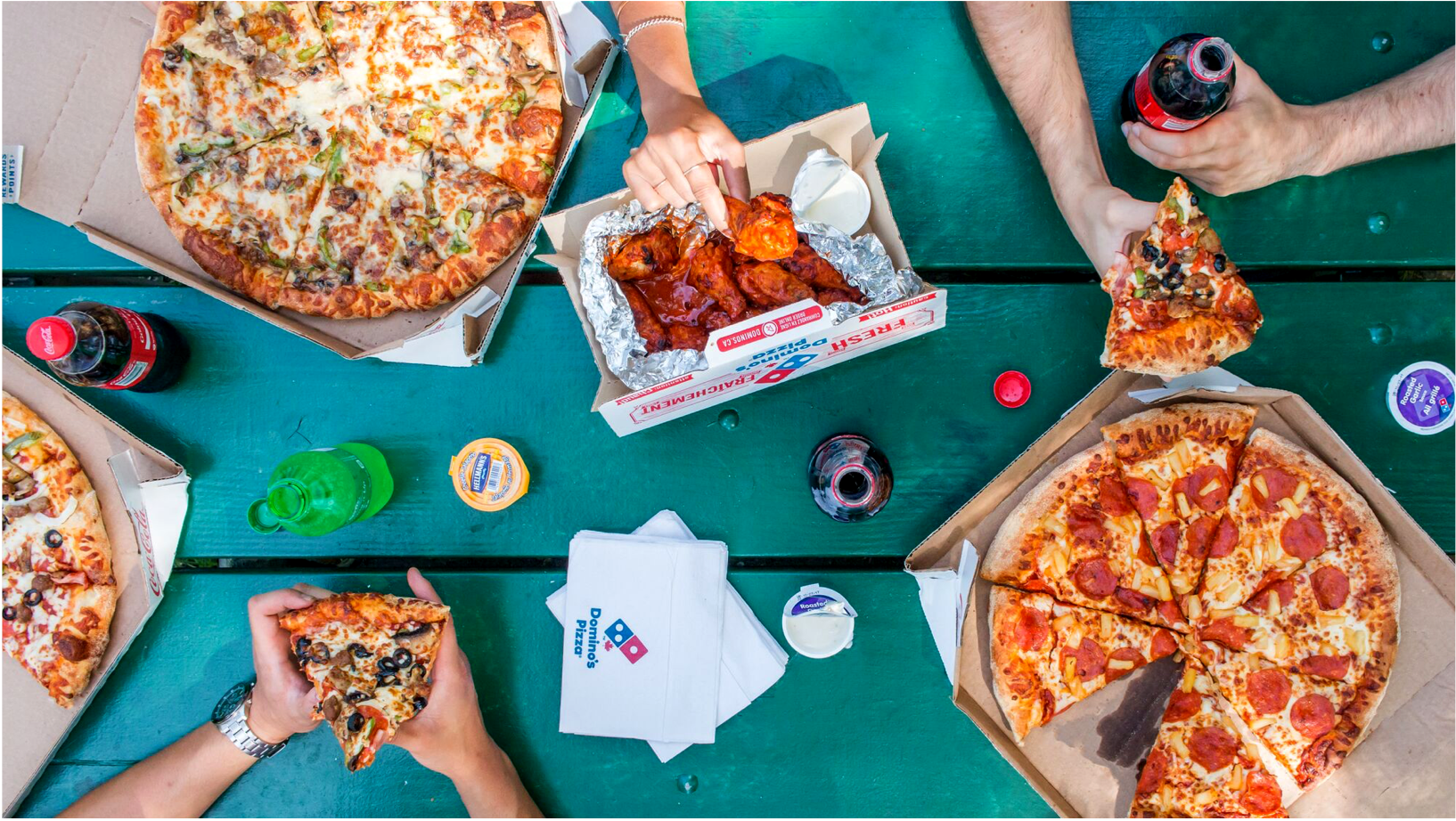 A picture taken from above showing people's hands sharing Domino's pizza and wings