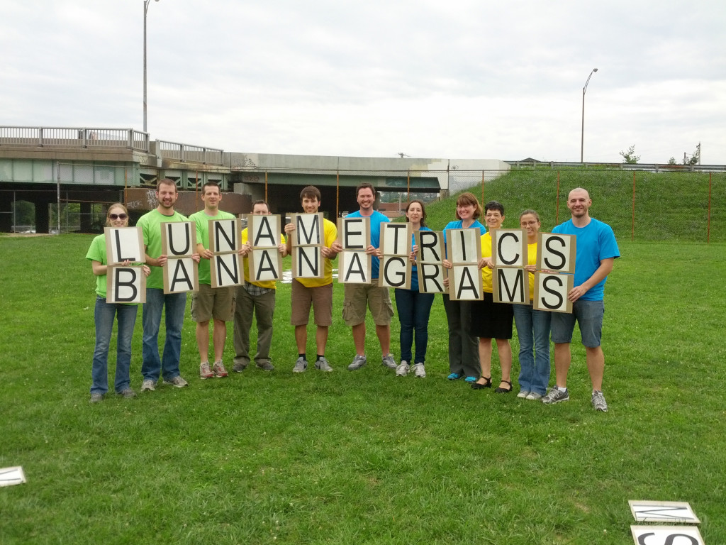 The LunaMetrics team poses with giant bananagrams tiles that spell 'LunaMetrics Bananagrams'