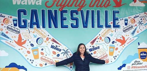 Woman in front of wawa gainesville mural