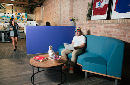 photo of interior of chicago office with employee sitting on couch and another walking by